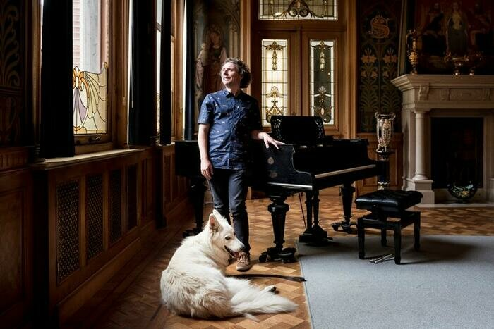Harr Viaene et son chien Oreo à côté d'un piano à queue dans le Jardin d'Hiver des Ursulines à Malines